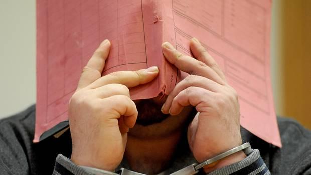 Niels H. versteckt sich im Gerichtssaal hinter einem Aktenordner