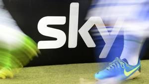 Zwei Fußball-Spieler laufen an einem Sky-Logo neben dem Platz vorbei