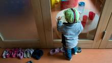 Ein Kleinkind steht an einer Glasscheibe in einer Kindertagesstätte in Dresden