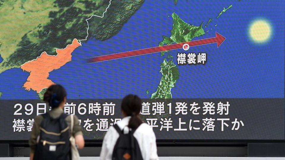 Zwei Frauen in Tokio schauen auf einen Riesen-Bildschirm. Darauf ist eine Karte Japans zu sehen mit der Flugbahn der Rakete