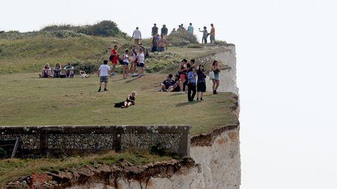 Menschen stehen an den Klippen in der Nähe von Eastbourne, Großbritannien