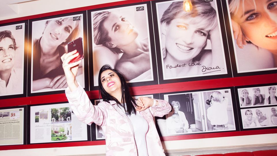 """Ihre Popularität ist ungebrochen. Ein Fan fotografiert sich vor Porträts im """"Café Diana"""""""