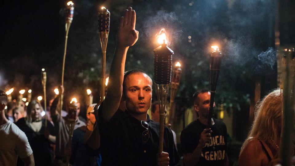 """Es waren Fackelträger wie diese, die Präsident Trump vor aller Welt nach einem Wochenende der Gewalt verteidigte. Sie zogen durch Charlottesville und skandierten """"Hail Trump!"""". Am Tag darauf starb eine Frau, als ein Rassist in die Menge der Gegendemonstranten fuhr"""