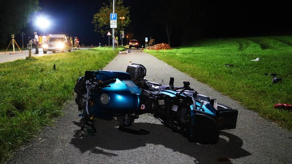 Das Motorrad des Unfalls im Allgäu liegt seitlich auf dem Gehweg.