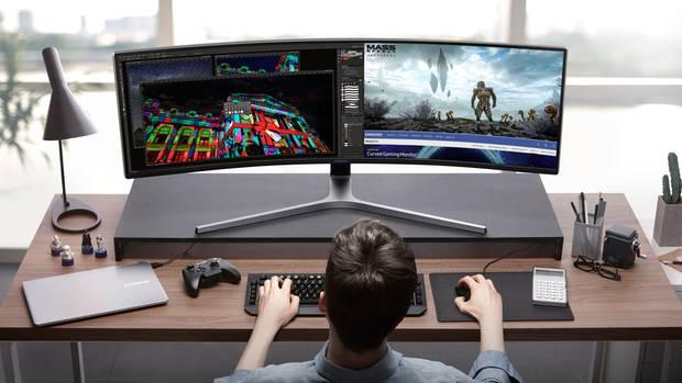 Ein Junger Mann sitzt vor seinem Samsung CHG90 Monitor