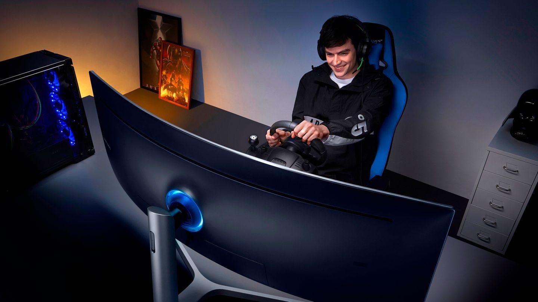Ein junger Man spielt mit einem Lenkrad auf dem Samsung CHG90 Monitor