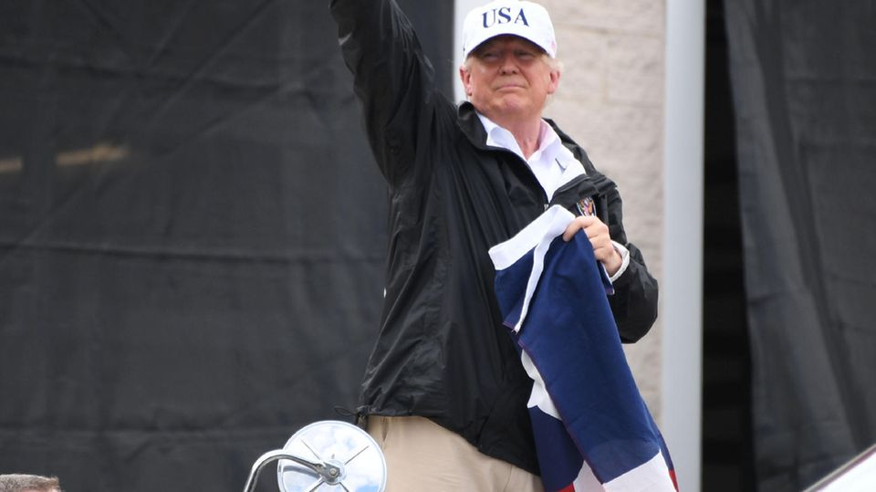 """Donald Trump winkt Menschen in Corpus Christi. """"Was für eine Menge!"""", sagt er. In der Hand hält er die texanische Flagge."""