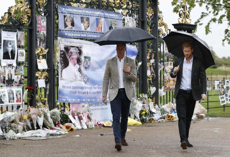 William und Harry schauen sich vor dem Kensington Palast niedergelegte Blumen an