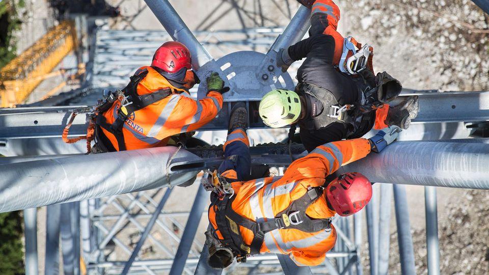 Balanceakt: Die Männer bereiten an der Spitze des Pfeilers die Seilmontage vor