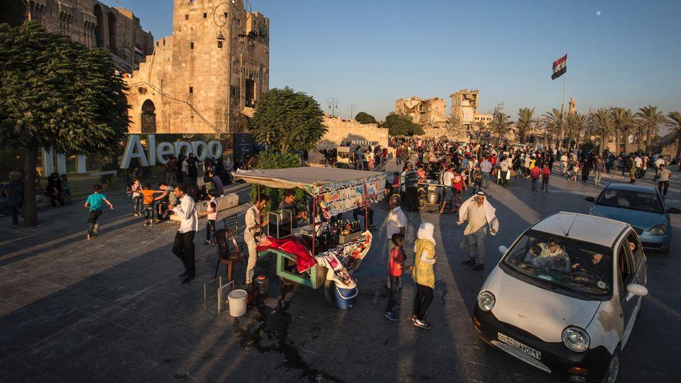 """Zwischen Zitadelle und ausgebombten Häusern treffen sich die Menschen wieder. """"Believe in Aleppo"""" steht am Rand des Platzes: Glaub an diese Stadt"""