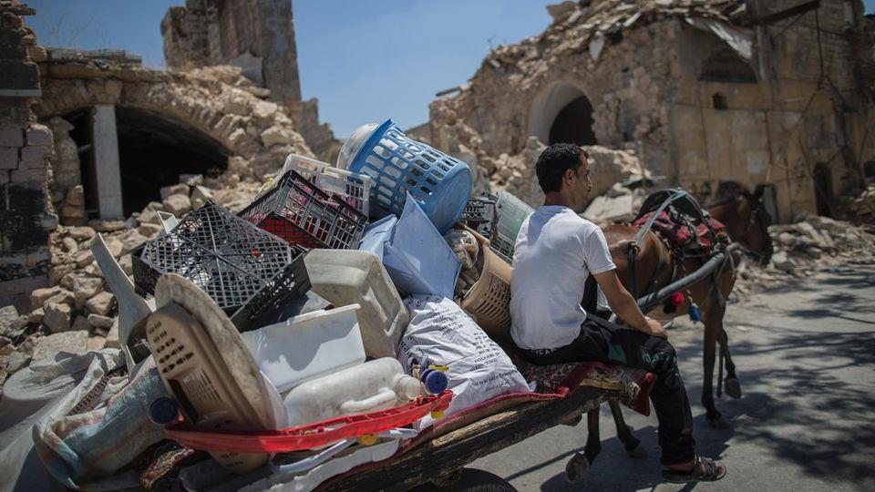Die meisten Straßen von Aleppo sind weiter menschenleer. Ein Mann transportiert Plastikabfall durch die Stadt