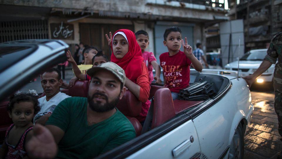 Diese Familie ist in ihrem Cabrio auf dem Weg zur Zitadelle im Zentrum. Die Überlebenden wollen sich zeigen, wollen Normalität