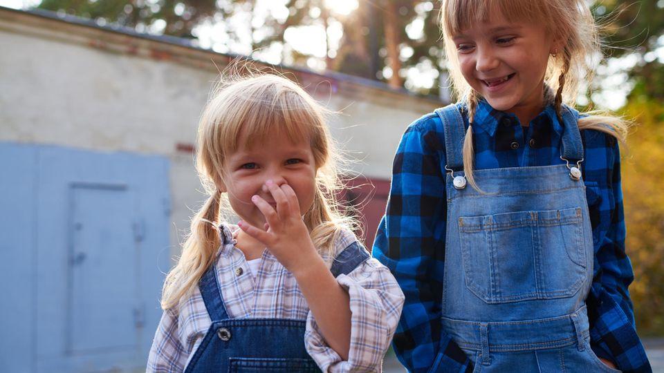 Zwei Mädchen in Latzhosen, eins popelt in der Nase