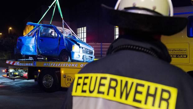 Das Fahrzeugwrack wird nach dem Zusammenstoß eines Autos mit einem ICE an der Bahnstrecke bei Bönen in Nordrhein-Westfalen aus einem Gebüsch auf ein Bergungsfahrzeug gehoben.