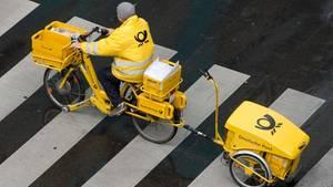 Briefzustellung bald nur noch an wenigen Wochentagen? Ein Briefträger der Deutschen Post ist mit einem E-Bike unterwegs.
