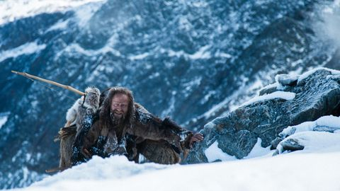 Mit langen Haaren und Vollbart klettert Jürgen Vogel in der Rolle des Ötzi über eine schneebedeckte Felskante