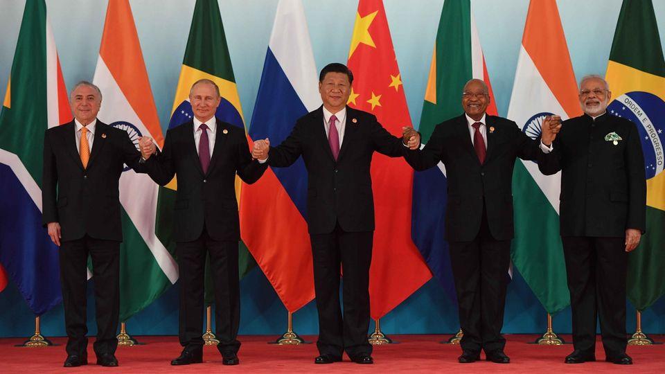 Die fünf Regierungschef der Brics-Staaten halten sich an den Händen auf dem roten Teppich in Xiamen, China.