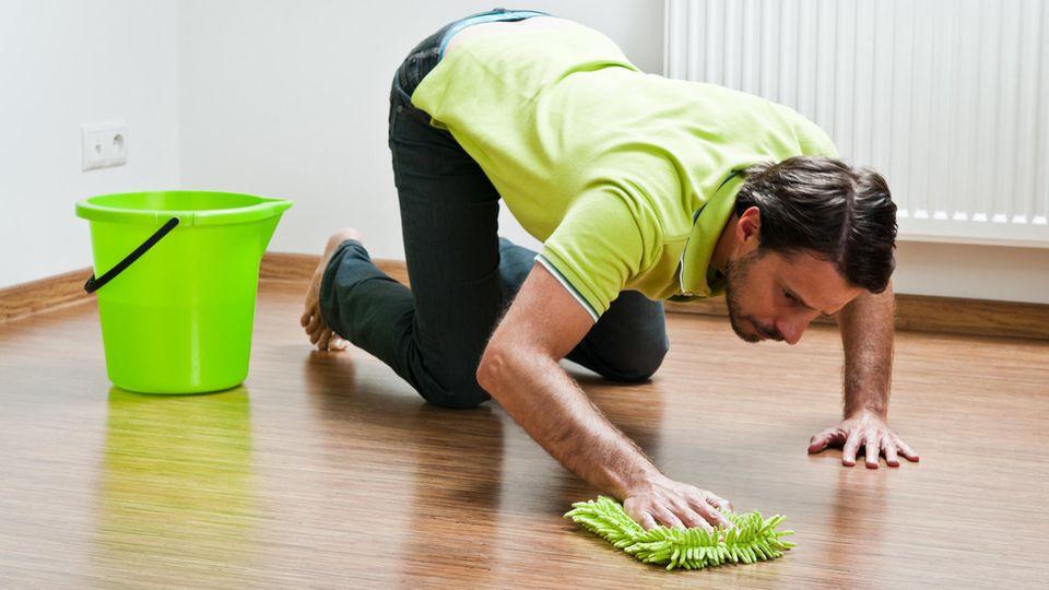 Mann kniet putzen am Boden