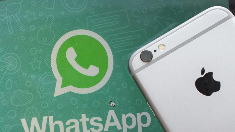 Ein iPhone liegt neben einem Bildschirm mit dem Whatsapp-Logo