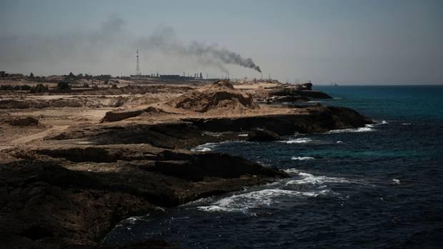 Die Ölraffinerie von Zawiya schickt Rauch in den Himmel. In der Nähe starteten bisher auch die Flüchtlingsboote
