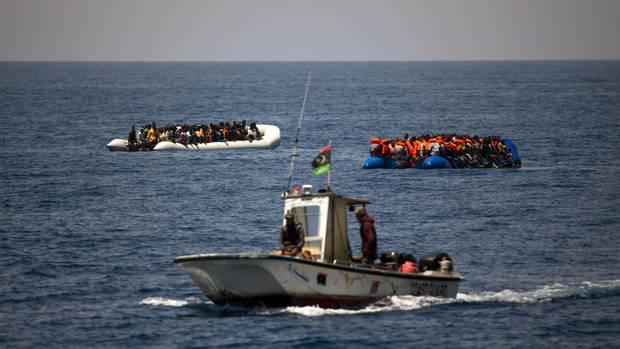 Ein kleines Boot der libyschen Küstenwache kreuzt vor zwei Schlauchbooten