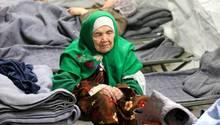 Die 106-Jährige Frau sitzt auf einem Feldbett in einem Zeltlager in Kroatien