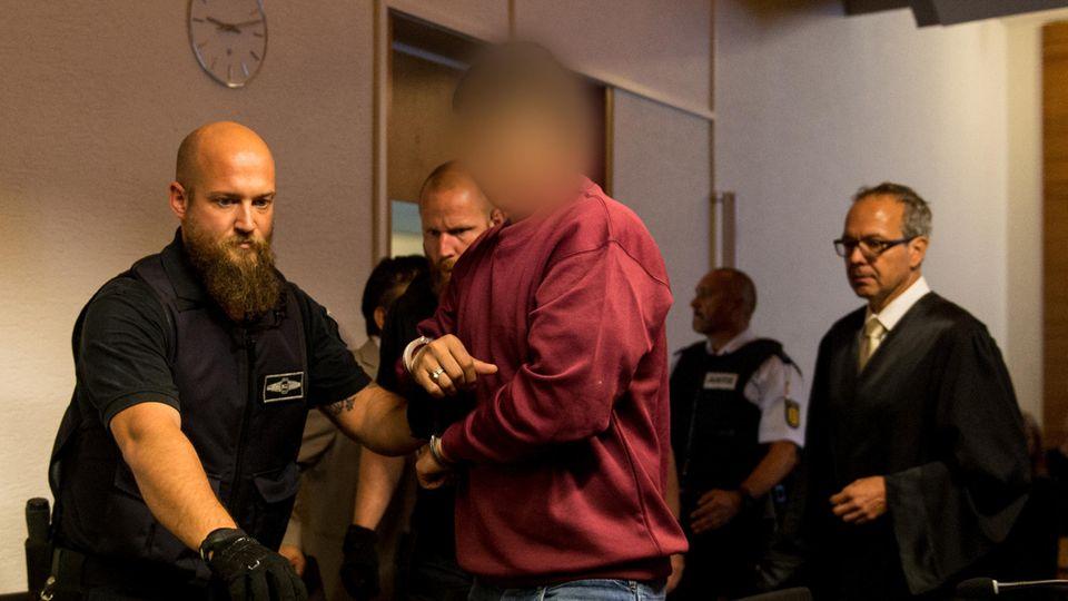 Hussein K. trägt ein weinrotes Sweatshirt, als er in Handschellen von Justizbeamten in den Gerichtssaal in Freiburg geführt wird