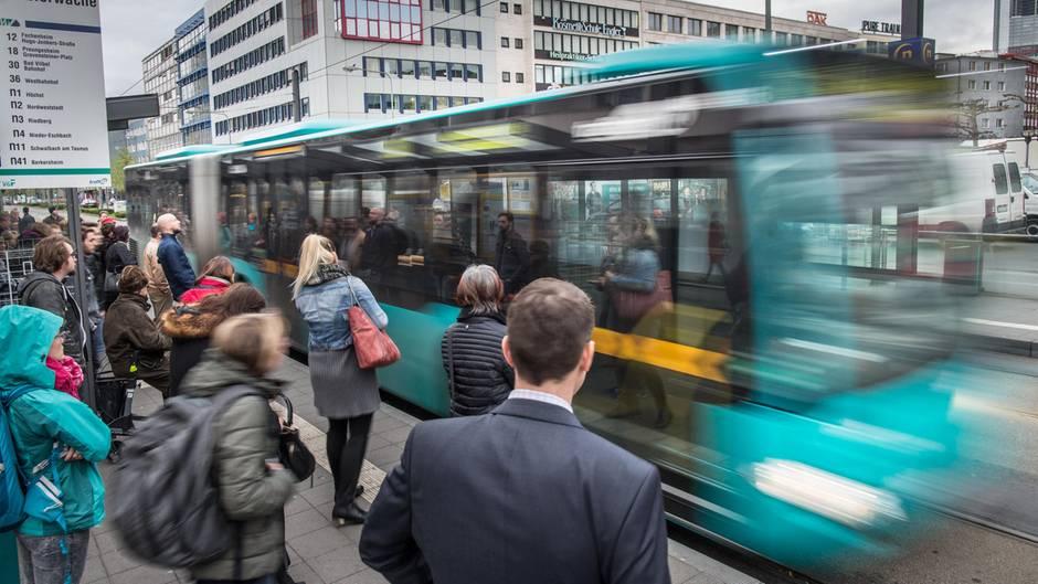 An der Konstablerwache in Frankfurt stehen Menschen und warten auf ihren Bus oder ihre Straßenbahn