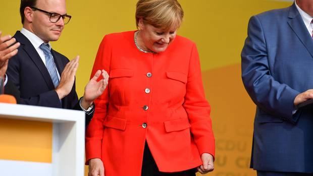 Bundeskanzlerin Angela Merkel schaut bei einer Wahlkampfveranstaltung in Heidelbergauf einen Fleck auf ihrer Jacke. Aus dem Publikum hatte jemand eine Tomate auf einen Tisch geworfen, der vor ihr stand