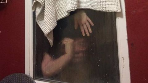 Die junge Frau hängt kopfüber im Fenster