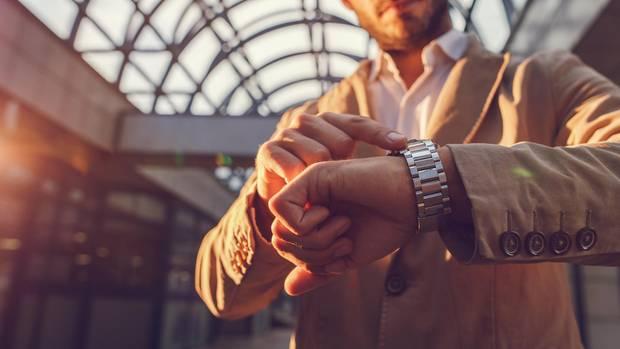 Ein Mann schaut auf seine Armbanduhr