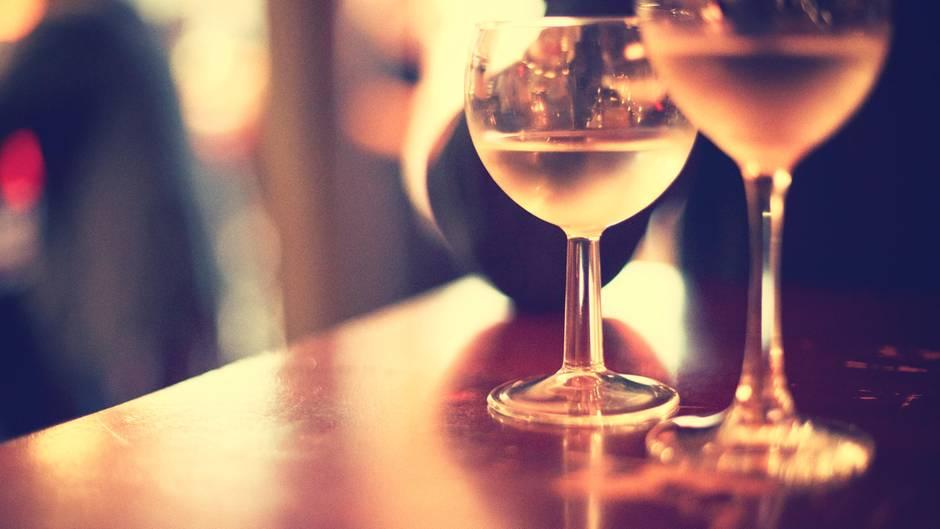 Zwei Weingläser stehen im gelbem Lichtschein einer Bar