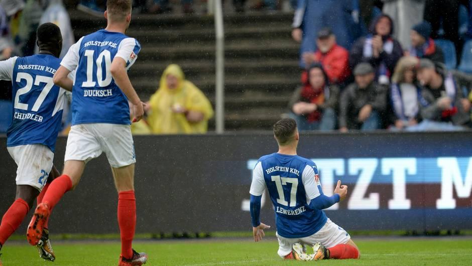 Der Kieler Torschütze Lewerenz rutscht nach seinem Treffer auf Knien Richtung Fans, zwei Mitspieler laufen hinterher