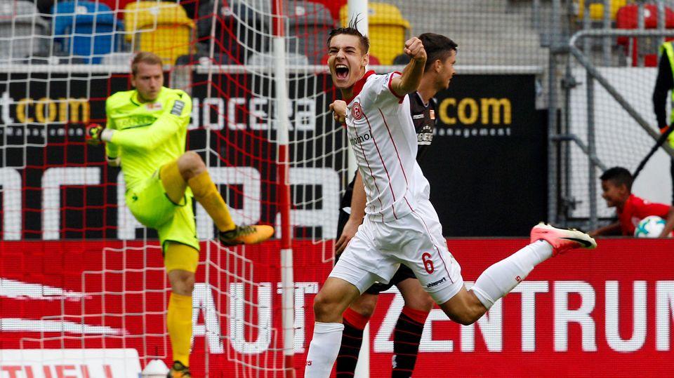 Florian Neuhaus (M.), der Düsseldorfer Torschütze zum 3:2, dreht jubelnd ab. Beim Berliner Torwart ist der Ärger groß