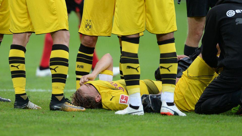 Marcel Schmelzer liegt rücklings auf dem Rasen, das gelbe BVB-Trikot vor das Gesicht gezogen. Zwei Betreuer knien bei ihm