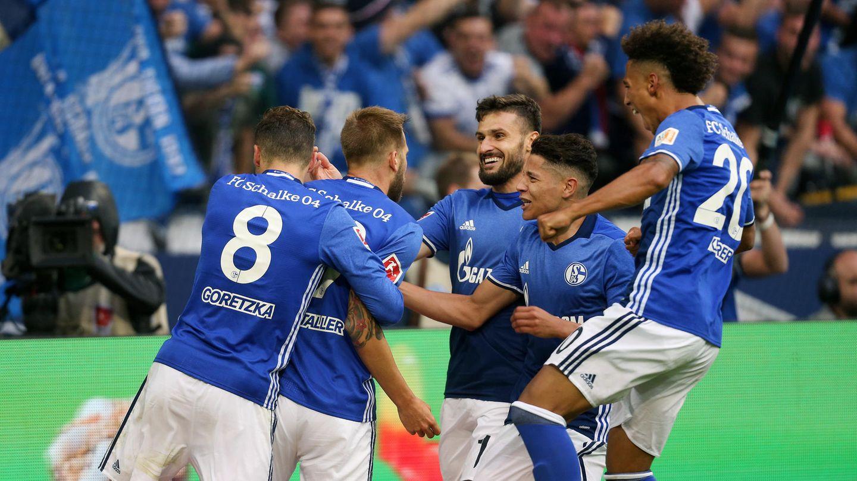 Leon Goretzka vom FC Schalke 04 umklammert den Torschützen Guido Burgstaller von hinten, drei weiter Schalker stürmen auf ihn zu