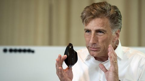 Logitech-CEO Bracken Darrell hält eine Maus des Unternehmens hoch
