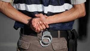 Türkei: Ein Polizist mit Handschellen am Gürtel steht in Silivri bei Istanbul vor einem Gerichtssaal