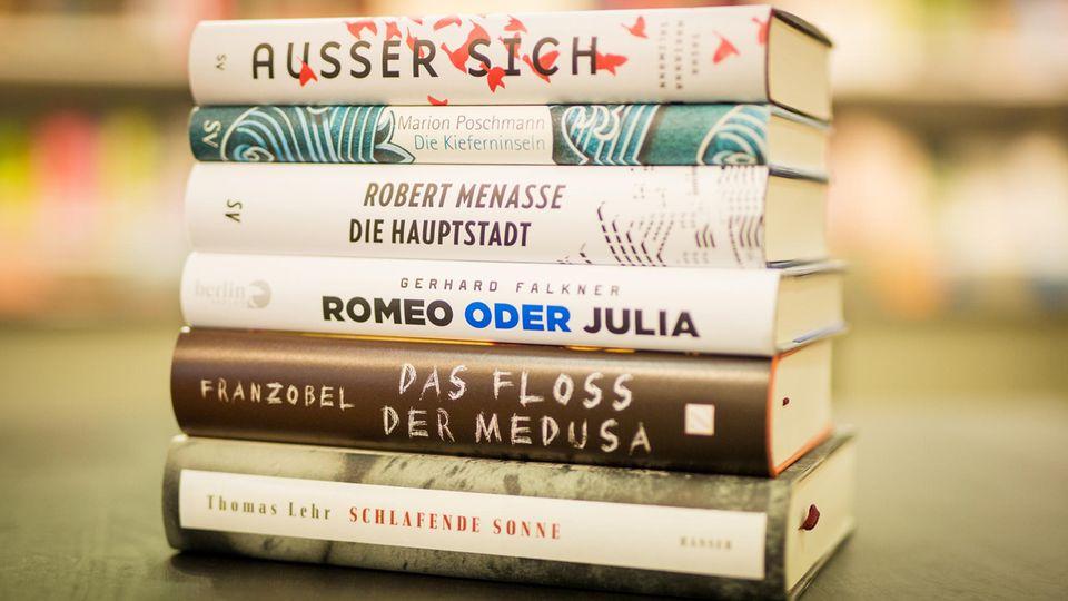 Deutscher Buchpreis: Die fünf Werke der Shortlist liegen übereinander gestapelt auf einem Tisch