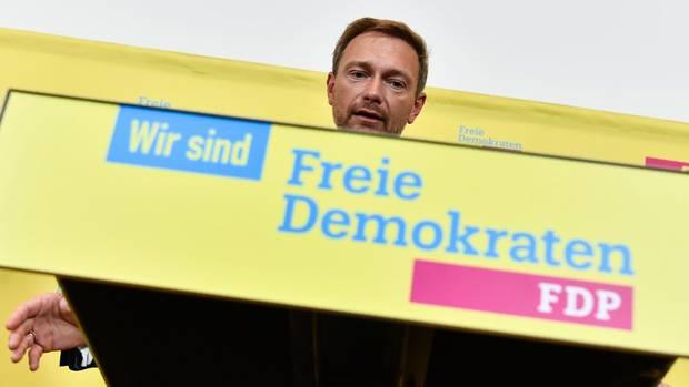 """Christian Lindner zeigt ein Schild mit der Aufschrift """"Wir sind Freie Demokraten - FDP"""" - Er sieht keine Steuerschuld"""
