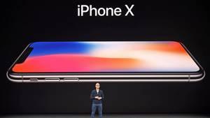 Tim Cook steht bei der Apple-Keynote vor einem Bild des iPhone X