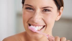"""Tipp 1: Qualität geht vor Quantität  Die Mehrheit der Fachleute empfiehlt, nur zweimal täglich zu putzen, morgens und abends. Mindestens einmal täglich sollten die Zähne auf allen Flächen gesäubert werden, inklusive Zwischenräumen.  """"Wenn Qualität vor Quantität geht, reicht unter Umständen auch einmaliges Putzen"""", erklärt Zahnexpertin Nicole Arweiler. Denn Plaque, also Ablagerungen aus Bakterien und Eiweißen, bildet sich zwar nach jedem Putzen neu. Bis dieser Belag krankheits- und kariesfördernd wirkt, vergehen jedoch viele Stunden. Eher schädlich als förderlich: gleich nach einer Mahlzeit die Bürste anzusetzen. """"Da der Zahnschmelz speziell nach säurehaltigen Speisen besonders angreifbar ist, sollte erst nach etwa 30 bis 60 Minuten mit der Mundhygiene begonnen werden. Andernfalls könnte der angelöste Schmelz mit der Bürste weggeschrubbt werden"""", warnt die Professorin. Um den Säuregehalt im Mund zu normalisieren, rät sie zu einer Mundspülung nach dem Essen oder zuckerfreiem Kaugummi. Wer mit Orangensaft und Früchten in den Tag startet, sollte besser vor dem Frühstück putzen."""