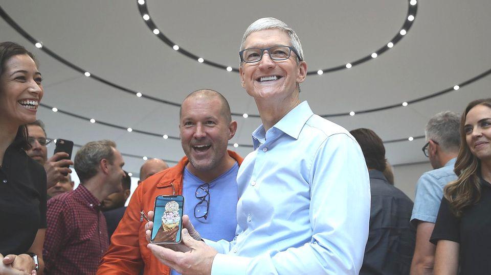 Apple-Chef Tim Cook zeigt das neue iPhone X. Eine Lampe über seinem Kopf wirkt wie ein Heiligenschein