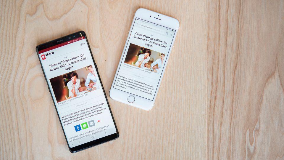 Ein Galaxy Note 8 und ein iPhone 6 liegen nebeneinander auf einem hellen Holztisch