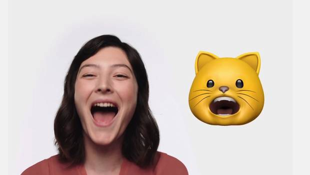 Eine Frau lacht mit offenem Mund, daneben imitiert das Katzen-Animoji ihre Mimik
