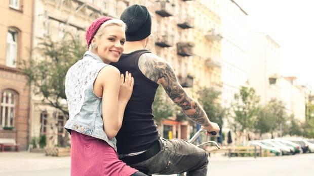 Ein junger Mann fährt Rad, auf dem Gepäckträger sitzt eine junge Frau