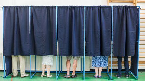 Wähler in Wahlkabinen
