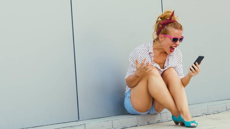 Eine Frau schreit wütend ihr Smartphone an