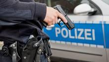 Ein Polizist hält seine Dienstwaffe vor einem Polizeiwagen (Symbolbild)