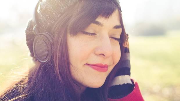 Eine Frau steht in der Sonne und hört mit einem Kopfhörer Musik